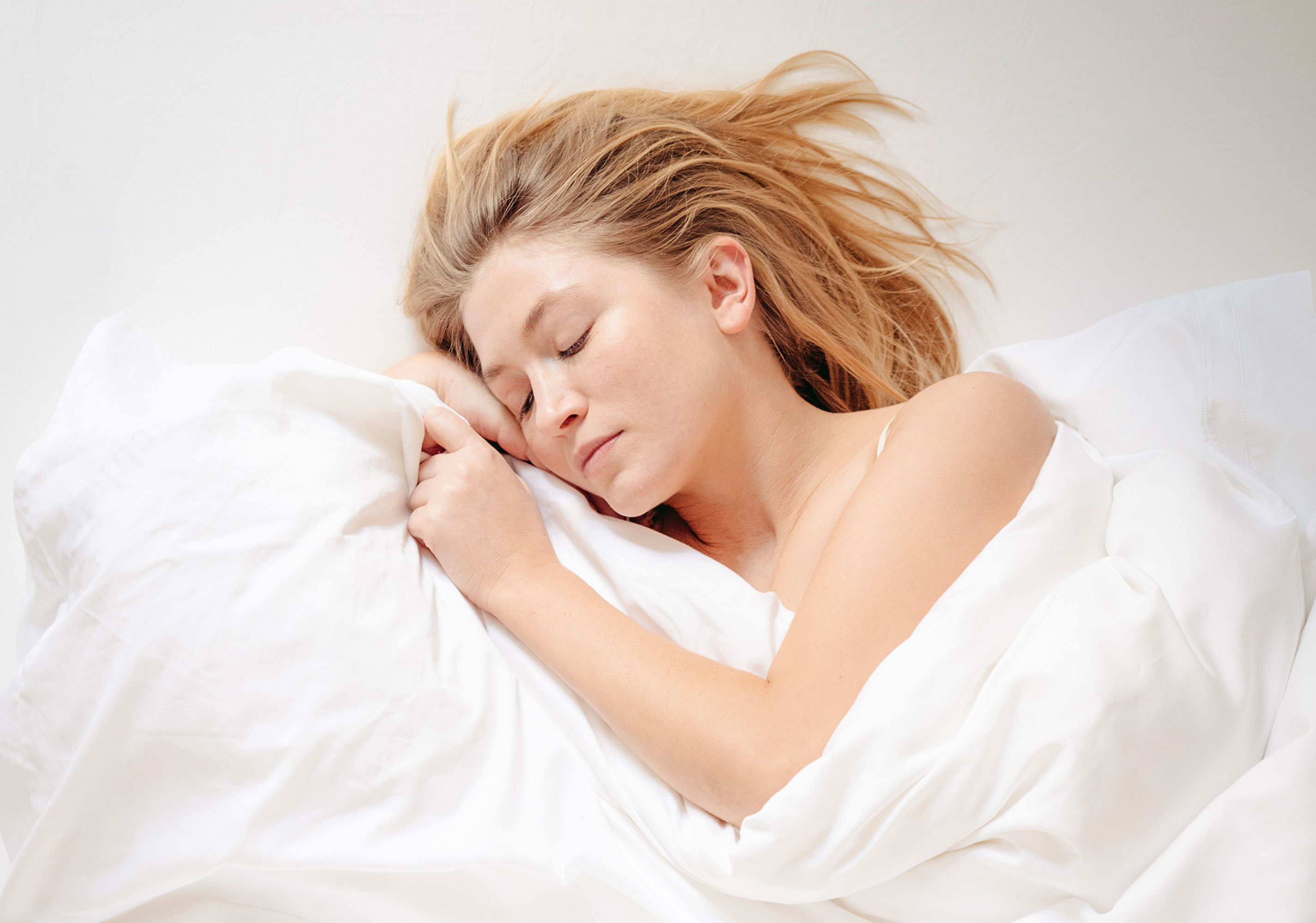 Frau in weißer Bettwäsche